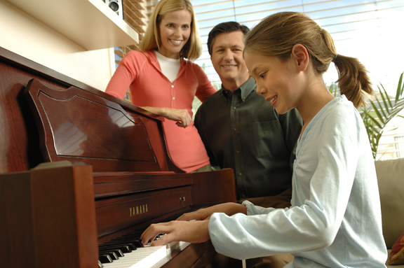 A family plays a vertical piano in their living room