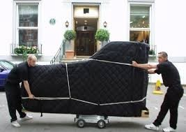 Two men move a piano covered in black padding